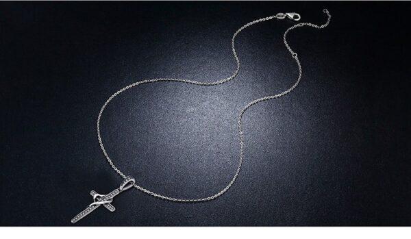 Pendentif croix en argent sertie de zircons portant un coeur stylisé