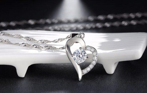 Pendentif coeur orné de cristaux recevant son imposant zircon blanc ou violet